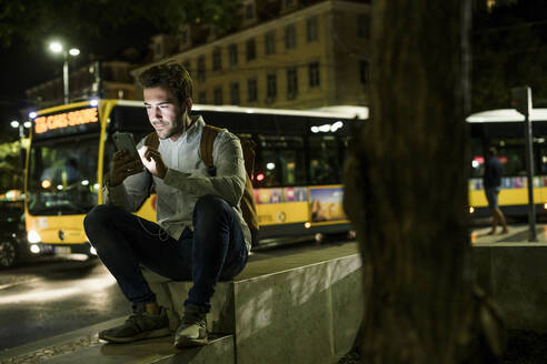 Portrait of young man using cell phone and earphones in the city by night, Lisbon, Portugal - UUF19187