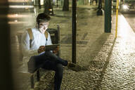 Portrait of laughing young man sitting at bus stop using digital tablet and earphones by night, Lisbon, Portugal - UUF19196