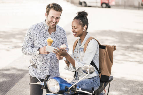 Happy young couple with motor scooter and ice cream using mobile phone in the city, Lisbon, Portugal - UUF19208
