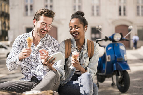 Happy young couple with ice cream using mobile phone in the city, Lisbon, Portugal - UUF19211