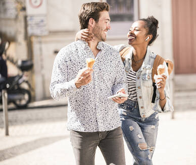 Happy young couple with ice cream and mobile phone in the city on the go, Lisbon, Portugal - UUF19217