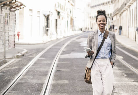 Smiling young woman with mobile phone in the city on the go, Lisbon, Portugal - UUF19229