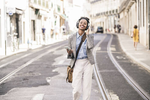 Happy young woman with headphones and mobile phone in the city on the go, Lisbon, Portugal - UUF19232