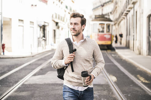 Smiling young man with backpack and coffee mug in the city on the go, Lisbon, Portugal - UUF19238