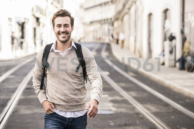 Portrait of smiling young man with backpack in the city on the go, Lisbon, Portugal - UUF19241 - Uwe Umstätter/Westend61