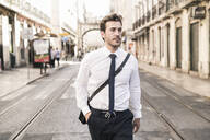 Confident young businessman in the city on the go, Lisbon, Portugal - UUF19253