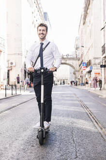 Happy young businessman riding e-scooter in the city, Lisbon, Portugal - UUF19256