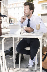 Young businessman using tablet and mobile phone at a cafe in the city, Lisbon, Portugal - UUF19265