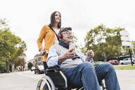 Young woman pushing senior man with headphones and smartphone in wheelchair - UUF19271