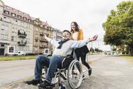 Smiling young woman pushing happy senior man in wheelchair - UUF19274
