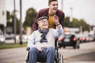 Portrait of laughing young man pushing happy senior man in wheelchair - UUF19286
