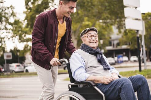 Young man pushing happy senior man in wheelchair - UUF19289