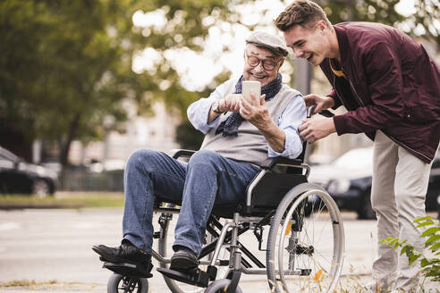 Laughing senior man in wheelchair and his adult grandson looking together at smartphone having fun - UUF19292