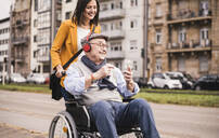 Smiling young woman pushing happy senior man with headphones and smartphone in wheelchair - UUF19298