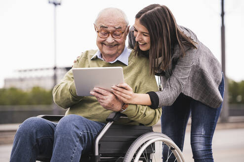 Senior man sitting in wheelchair and adult granddaughter looking together at digital tablet - UUF19313