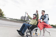 Young man pushing senior man sitting in a wheelchair dressed up as superhero - UUF19316