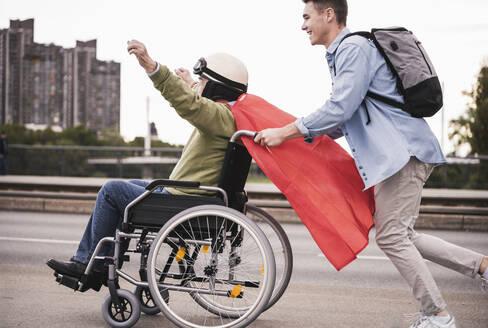 Young man pushing senior man sitting in a wheelchair dressed up as superhero - UUF19319