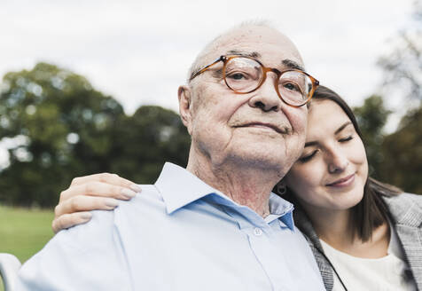 Portrait of self-confident senior man with his granddaughter in a park - UUF19325