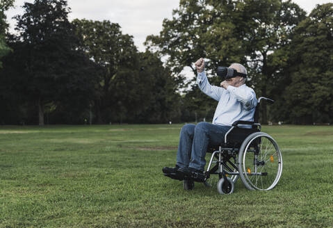Senior man sitting in wheelchair using Virtual Reality Glasses - UUF19352