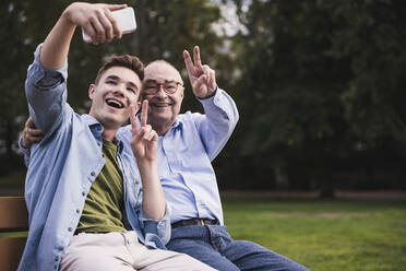 Senior man and grandson sitting together on a park bench taking selfie with smartphone - UUF19358