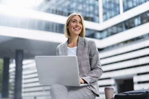 Smiling young businesswoman using laptop in the city - DIGF08636