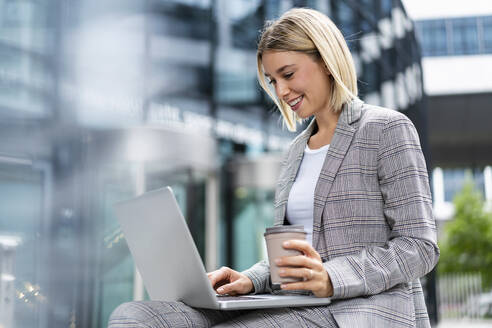 Smiling young businesswoman using laptop in the city - DIGF08639