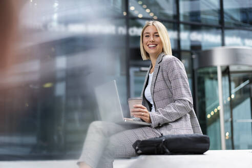 Portrait of happy young businesswoman with laptop in the city - DIGF08642