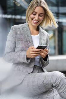 Happy young businesswoman using mobile phone in the city - DIGF08648
