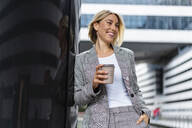 Happy young businesswoman with takeaway coffee in the city - DIGF08654