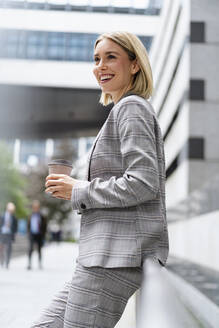 Happy young businesswoman with takeaway coffee in the city - DIGF08657