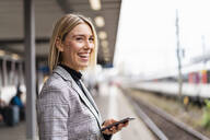 Happy young businesswoman with mobile phone at the train station - DIGF08663