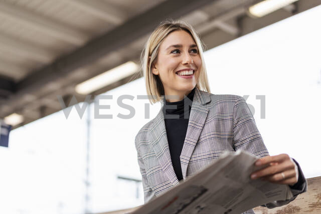 Smiling young businesswoman with newspaper at the train station - DIGF08666 - Daniel Ingold/Westend61