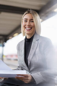 Portrait of happy young businesswoman with papers at the train station - DIGF08669