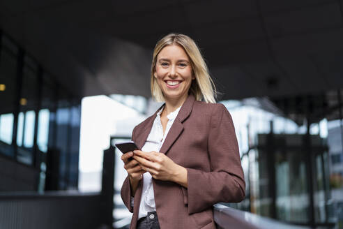 Portrait of happy young businesswoman with mobile phone in the city - DIGF08678