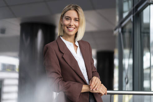 Portrait of confident young businesswoman leaning on railing - DIGF08684
