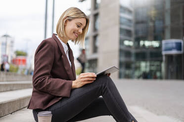 Smiling young businesswoman using tablet in the city - DIGF08693
