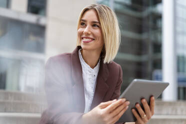 Smiling young businesswoman using tablet in the city - DIGF08699