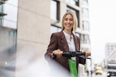 Portrait of happy young businesswoman with e-scooter in the city - DIGF08702