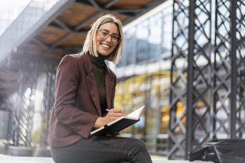 Portrait of happy young businesswoman with notebook in the city - DIGF08711