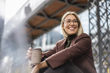Happy young businesswoman with takeaway coffee in the city - DIGF08714
