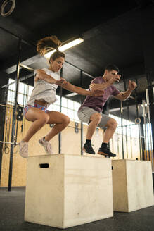 Young couple doing box jump exercise during cross training - MTBF00069