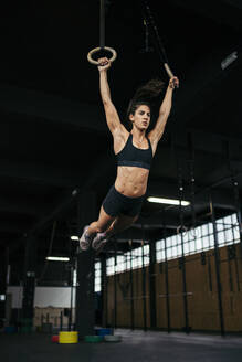 Young woman wearing black sportswear doing ring muscle up workout with gymnastic rings - MTBF00075