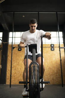 Athletic man doing air bike workout at gym - MTBF00078
