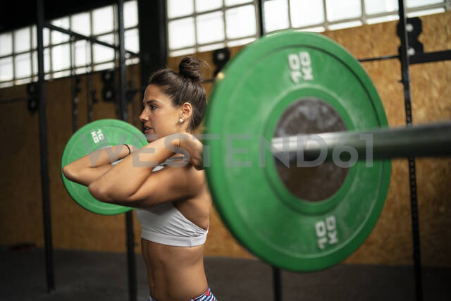 Young woman doing overhead squat exercise at gym - MTBF00084 - Mikel Taboada/Westend61