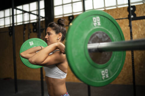 Young woman doing overhead squat exercise at gym - MTBF00084