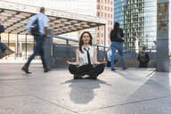 Young businesswoman practising yoga in the city at rush hour, Berlin, Germany - WPEF02180
