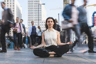 Young businesswoman practising yoga in the city at rush hour, Berlin, Germany - WPEF02183