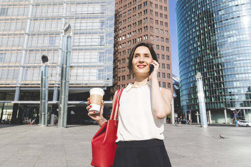 Smiling young businesswoman with takeaway coffee on the phone in the city, Berlin, Germany - WPEF02186