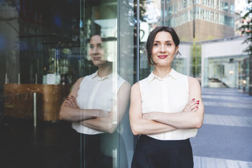 Portrait of confident young businesswoman reflected in glass front, Berlin, Germany - WPEF02195