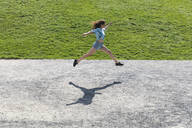 Young woman jumping and running outdoors in summer - WPEF02201